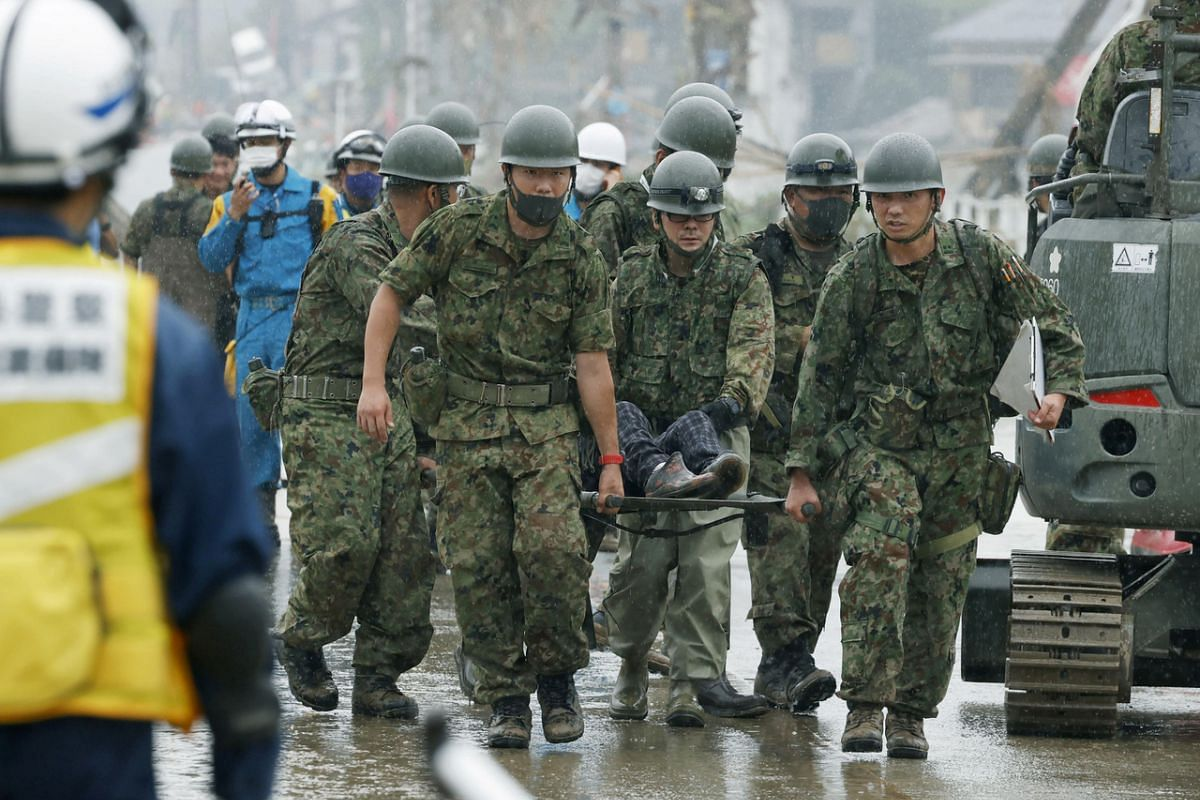 Japanese Self-Defence Force soldiers carry a rescued person using a stretcher at a flooding site caused by a heavy rain in Kuma village, Kumamoto prefecture, on July 5, 2020.