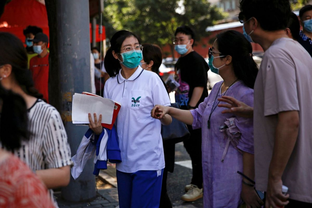 """Parents wish their daughter good luck as she enters a high school to take part in the annual national college entrance exam or """"gaokao"""", which had been postponed by one month due to the coronavirus disease outbreak, in Beijing, China July 7, 2020. PH"""
