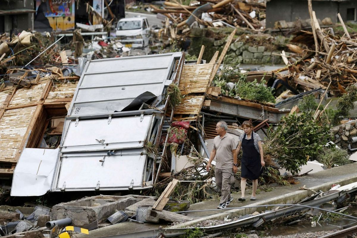 A couple visiting the site of their parents' house which was damaged by torrential rain in Kuma town, Kumamoto Prefecture, south-western Japan, in this photo taken by Kyodo, on July 6, 2020. PHOTO: KYODO VIA REUTERS