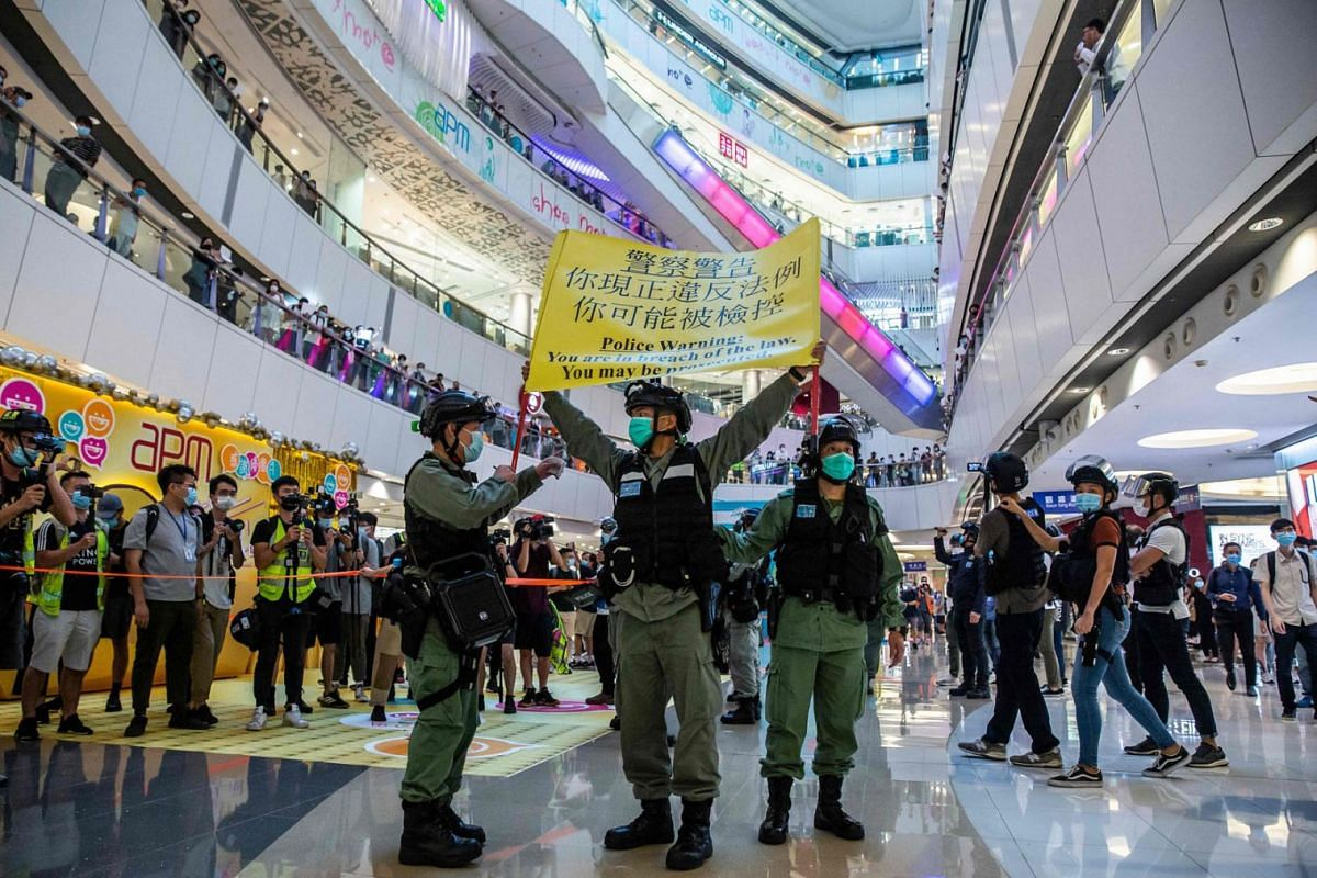 Riot police hold up a warning flag during a demonstration in a mall in Hong Kong on July 6, 2020, in response to a new national security law introduced in the city which makes political views, slogans and signs advocating Hong Kong's independence o