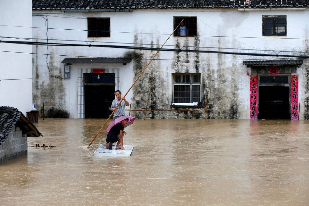 People using a makeshift raft to get around a flooded village following heavy rainfall in Huangshan, Anhui province, China July 6, 2020. PHOTO: CNSPHOTO VIA REUTERS