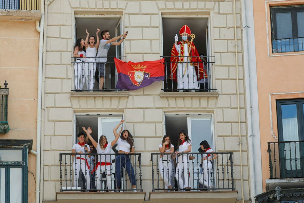 """A reveller dressed up as Saint Fermin waves from a balcony in front of the town hall where the firing of """"chupinazo"""", which opens the San Fermin festival that was cancelled due to the coronavirus disease outbreak, should have taken place, in Pamplona"""
