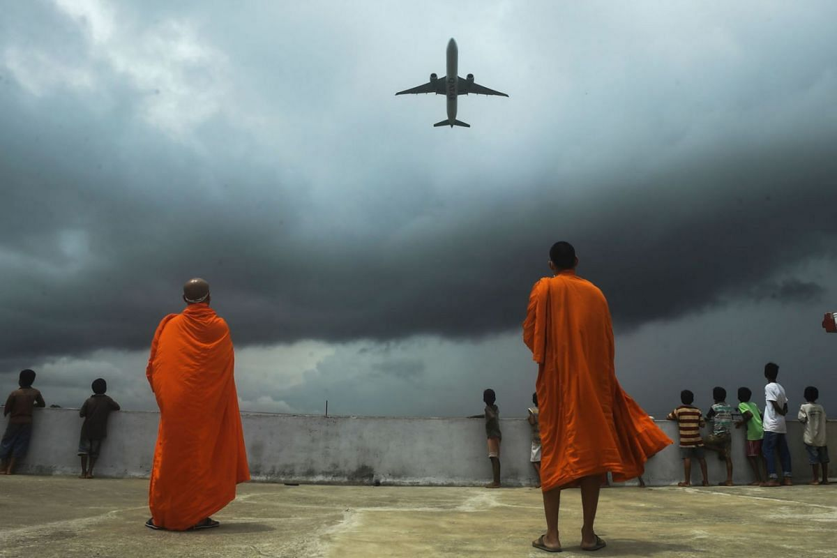Buddhists monks and children look out from the rooftop at a Buddhist mission hostel and school for underprivileged children as an international passenger flight takes off at the Netaji Subhash Chandra Bose International Airport in Kolkata on July 5,