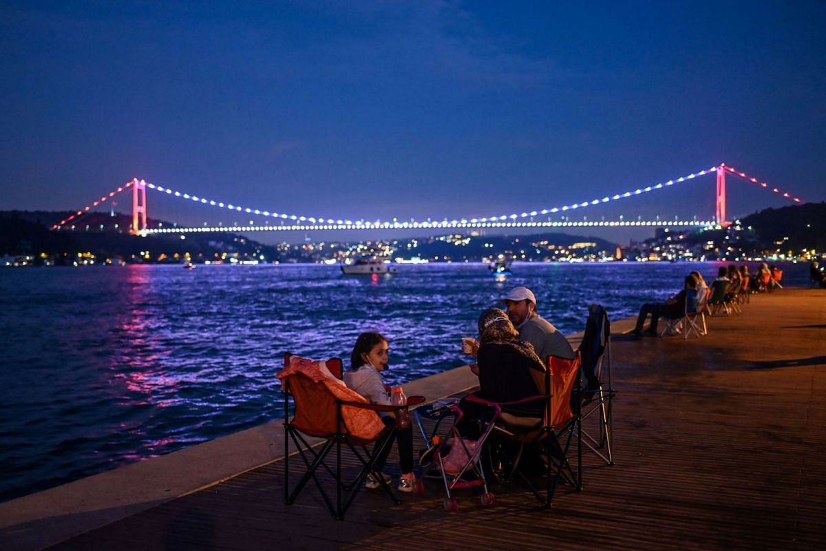 People enjoying the evening by the Bosphorus with the Fatih Sultan Mehmet bridge lit up in the background on July 6, 2020, in Istanbul. PHOTO: AFP