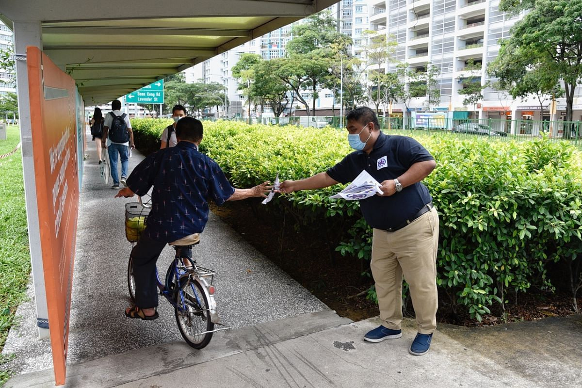 Jalan Besar Peoples Voice candidate Nor Azlan Sulaiman giving out fliers to a cyclist on July 6, 2020.