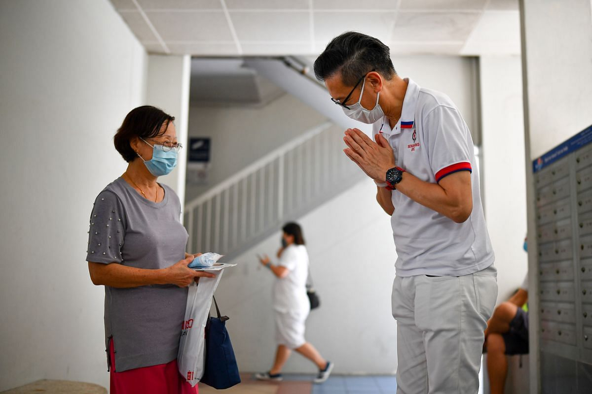 PAP's Mr Raymond Lye interacting with Sengkang GRC resident Jenny Aw at the void deck of Block 193 Rivervale Drive on July 6, 2020.