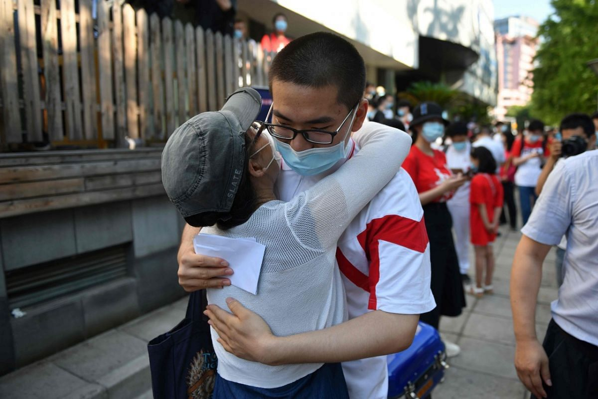 A student embraces his mother before entering a school to sit the National College Entrance Examination in Beijing on July 7, 2020.