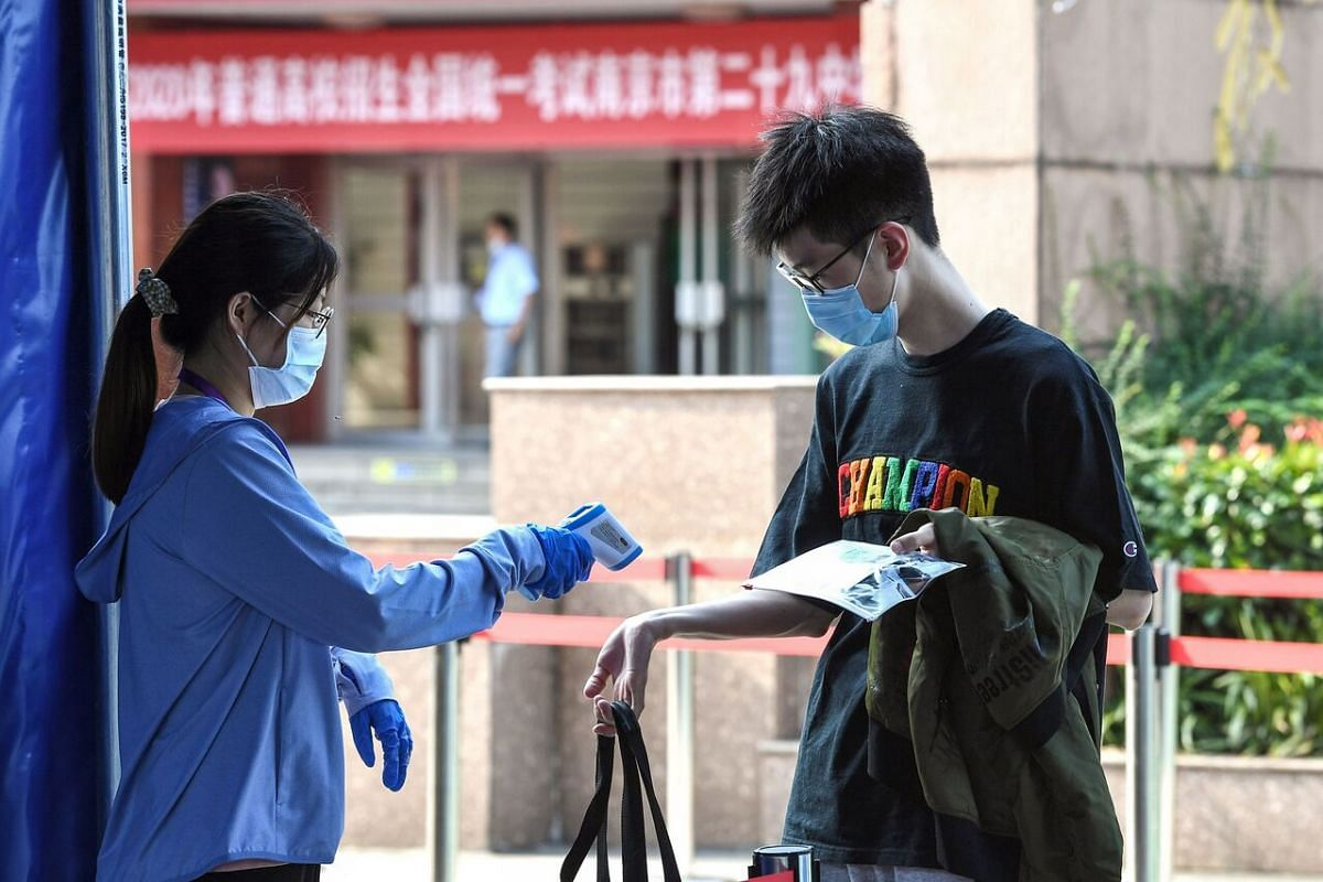 A student has his body temperature checked before entering a school to sit the National College Entrance Examination in Nanjing, China, on July 7, 2020.
