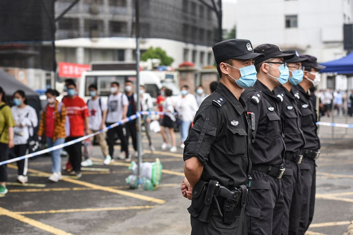 Police officers stand guard outside a school as students queue to enter before taking the National College Entrance Examination in Huaian, China, on July 7, 2020.