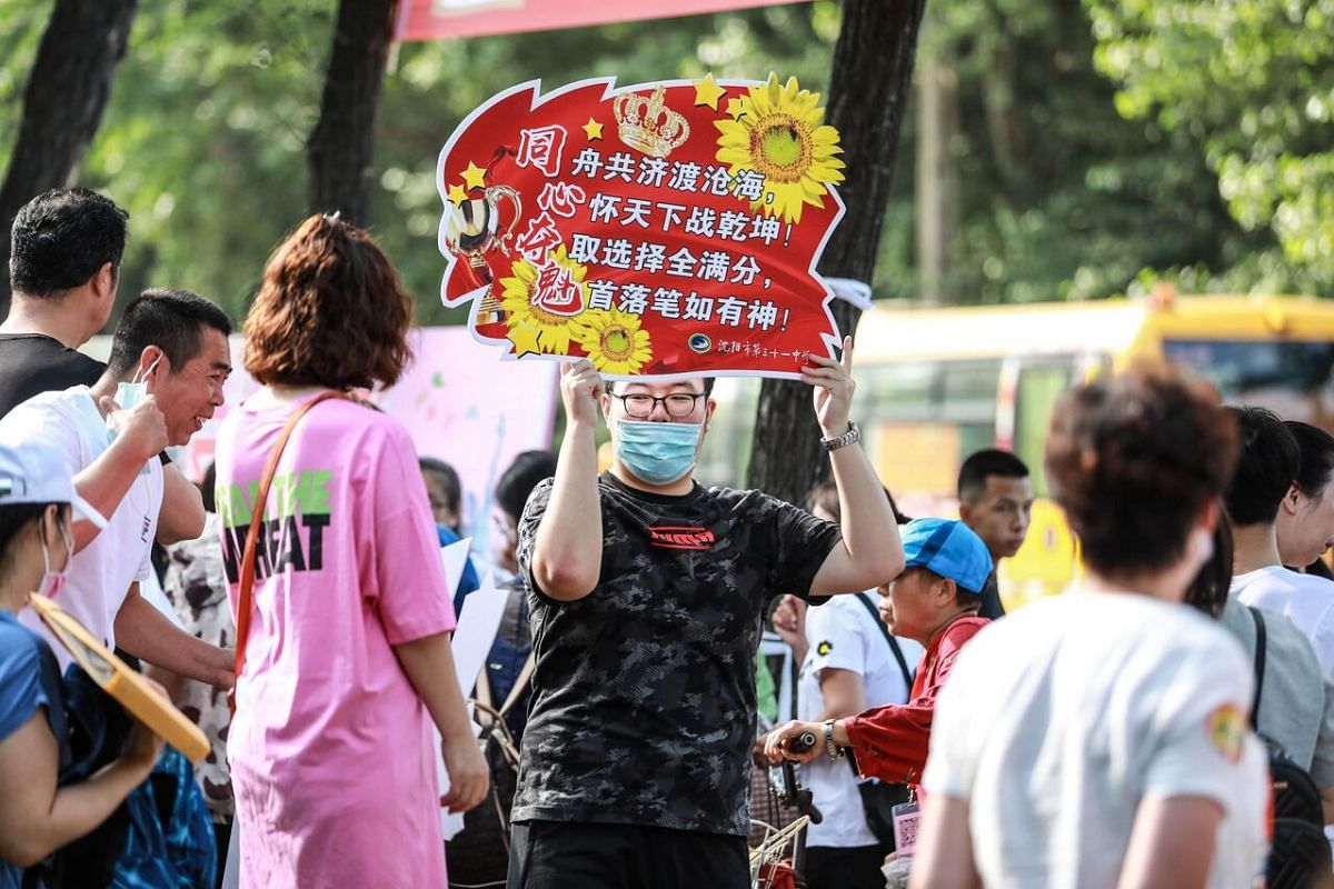 A man outside a school in Shenyang holds a sign encouraging students to have good results on their examination, on July 7, 2020.