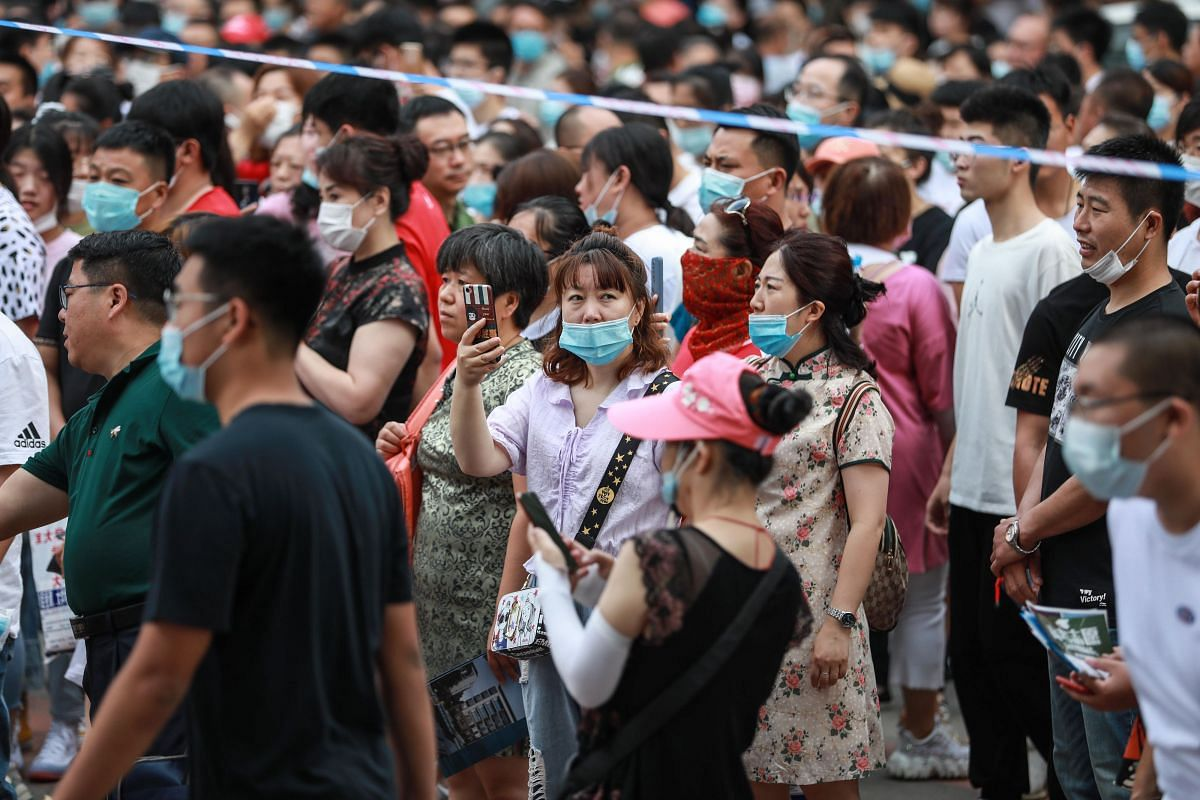 Parents wait outside a school as students take the National College Entrance Examination in Shenyang, China, on July 7, 2020.