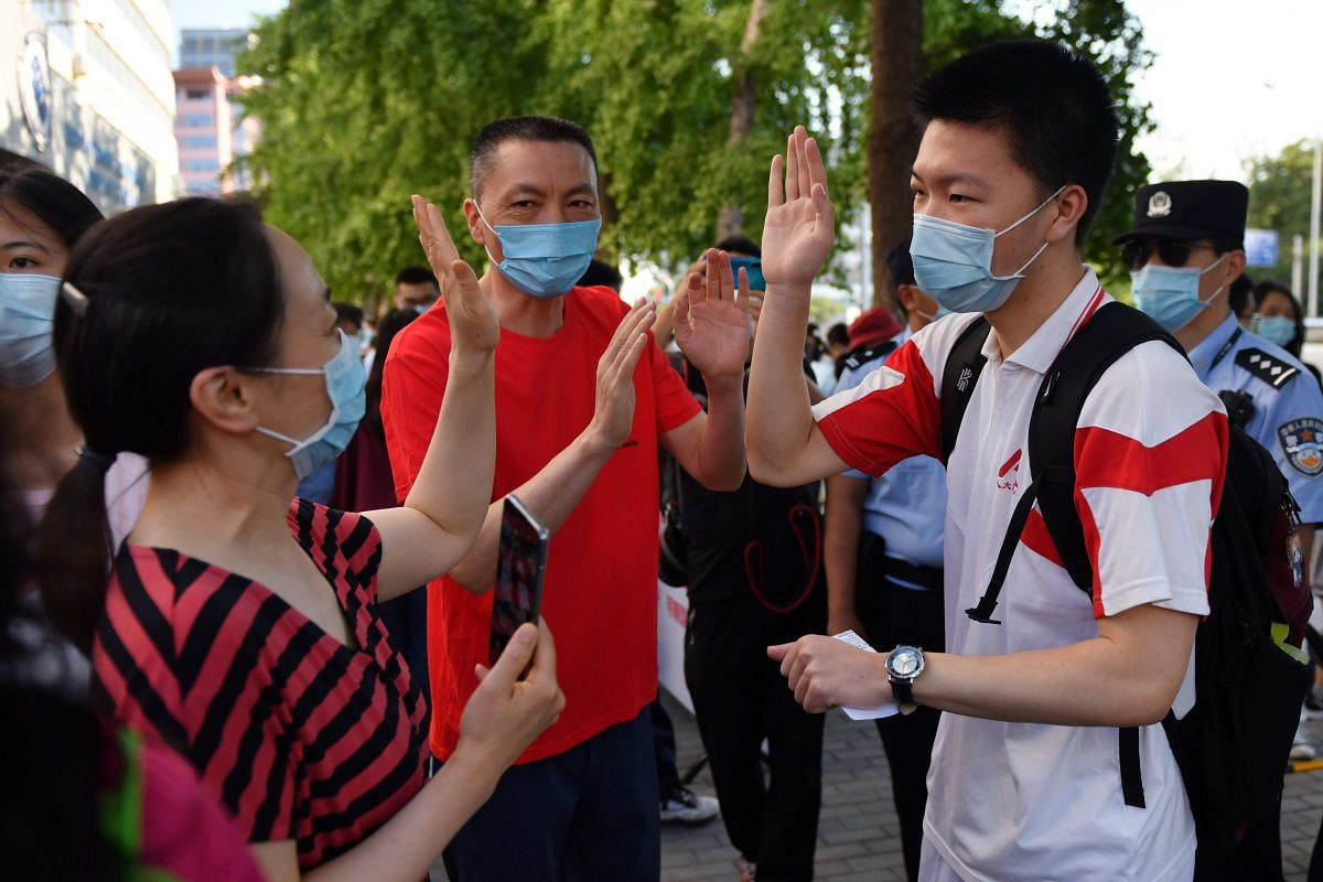 A student high-fives with his parents before entering a school to sit the National College Entrance Examination in Beijing on July 7, 2020.