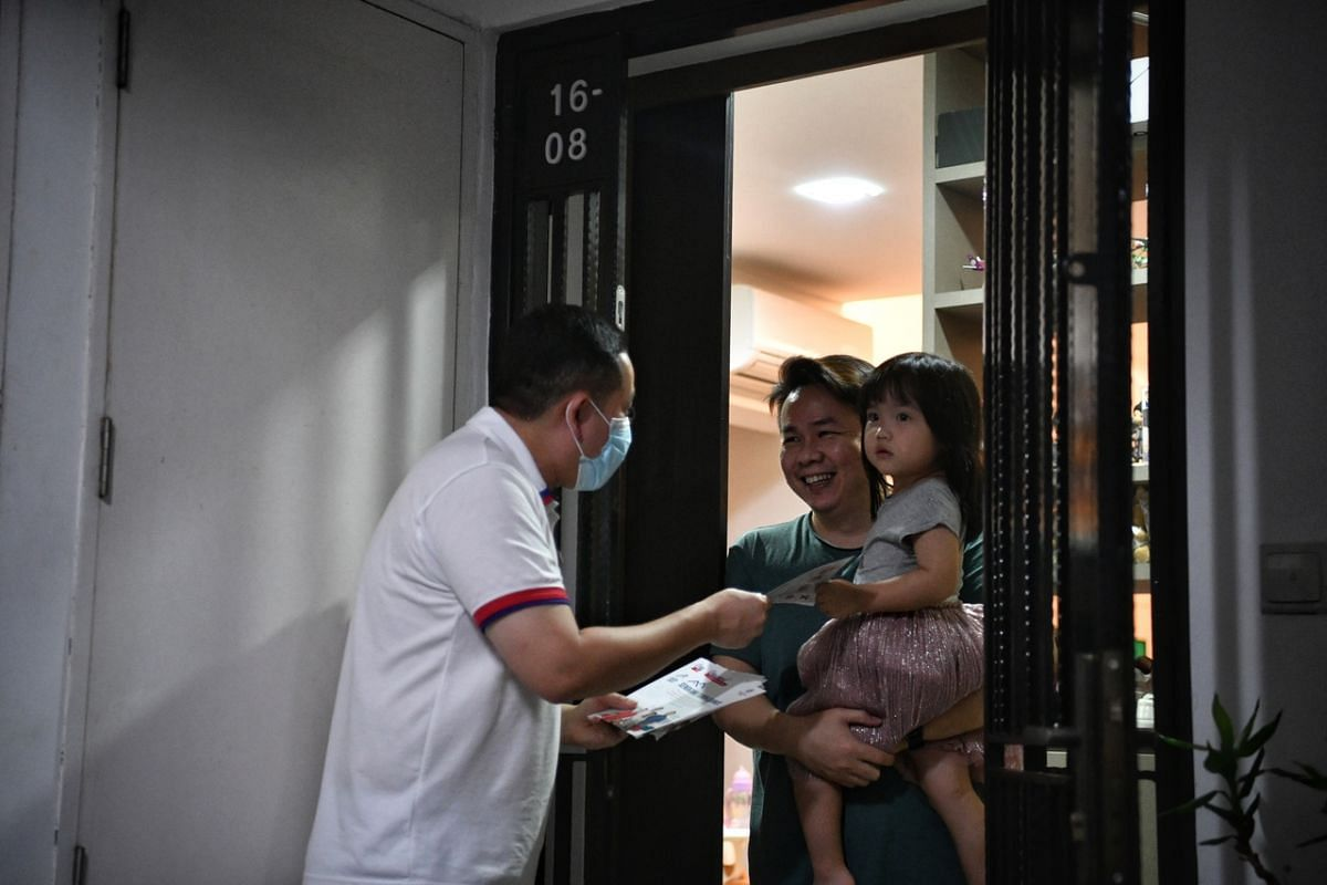 Senior Parliamentary Secretary for Home Affairs and Health Amrin Amin, who is a People's Action Party candidate for Sengkang GRC, interacting with a resident at Blk 334C Anchorvale Crescent on July 7, 2020.