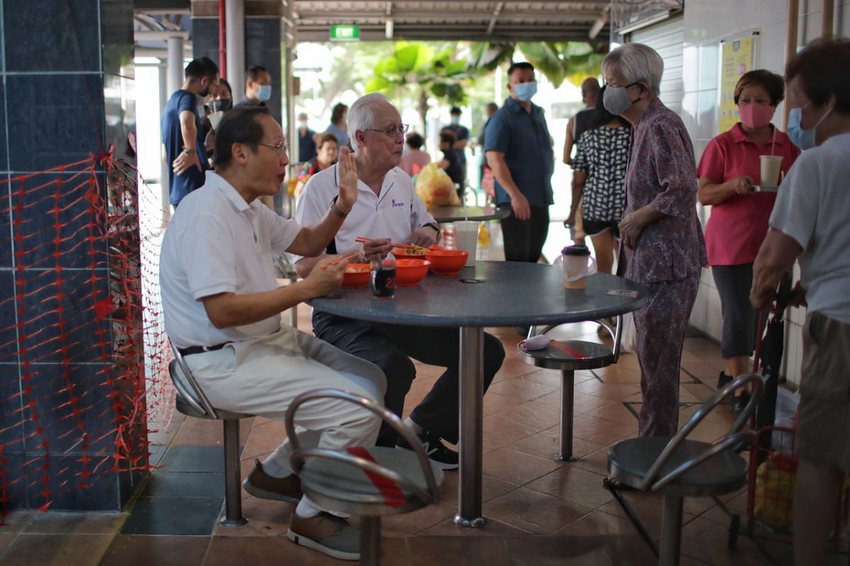 Emeritus Senior Minister Goh Chok Tong (second from left) and PAP candidate for Marine Parade GRC Tan See Leng greeting a resident while eating at Marine Terrace Market on July 7, 2020.