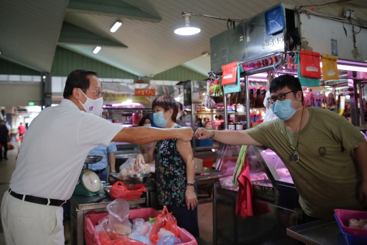 PAP candidate for Marine Parade GRC Tan See Leng with a stall owner during a walkabout at Marine Terrace Market on July 7, 2020.