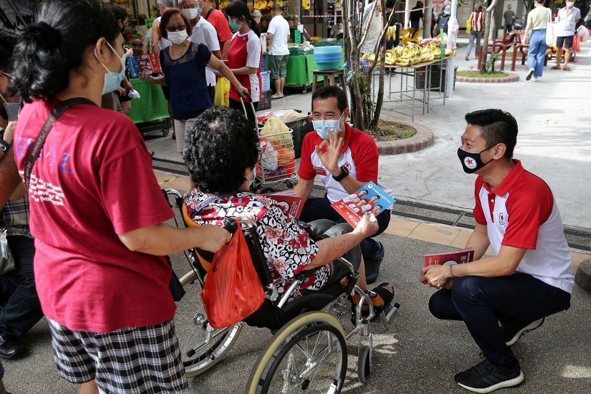 Singapore People's Party candidates for Bishan-Toa Payoh GRC Steve Chia (centre), who is the party's secretary-general, and Williiamson Lee interacting with an elderly resident during a walkabout at Kim Keat Palm Market and Food Centre on July 7,
