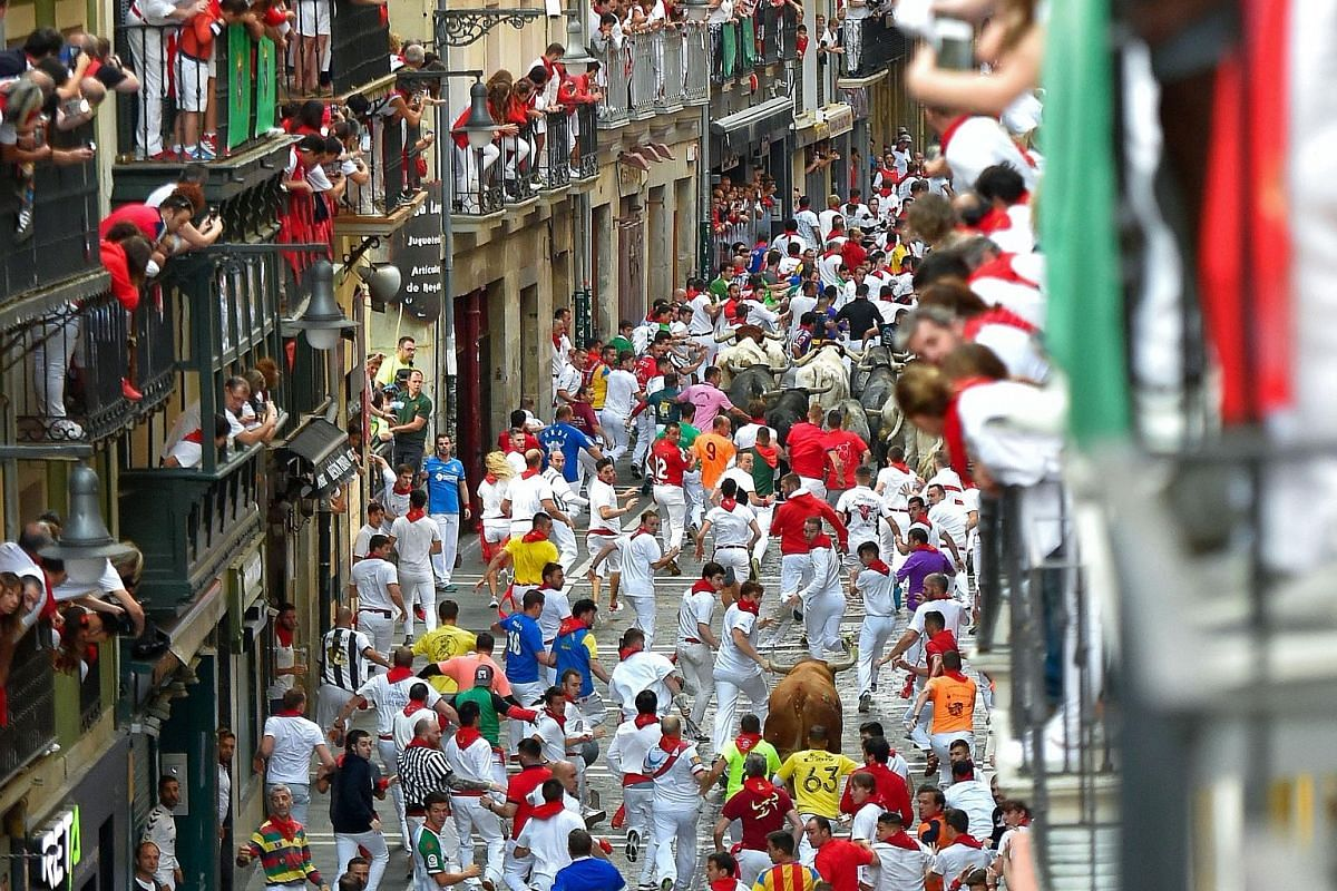 Usually, revellers from all over the globe would pack the streets (above) to watch or partake in the bull runs.