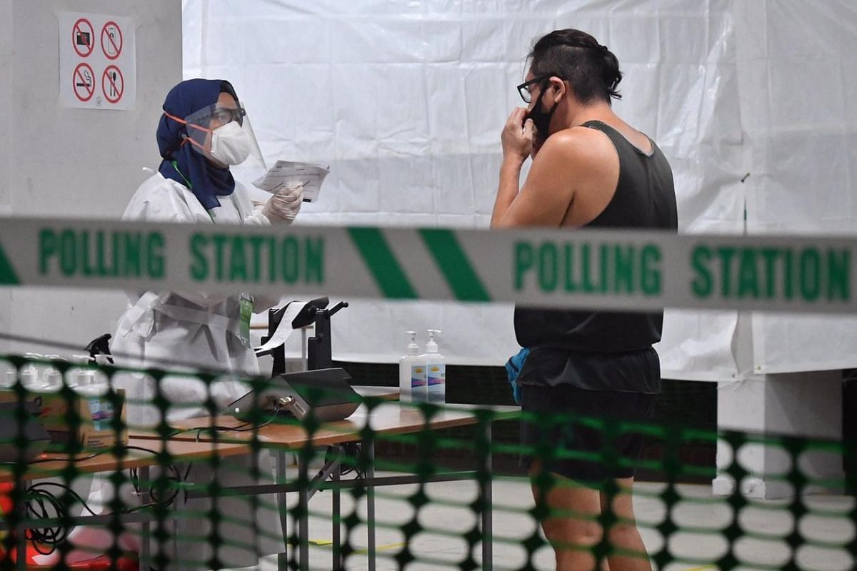 A voter pulls down his mask to verify his identity prior to casting his ballot at a polling station at 426 Ang Mo Kio Ave 3 on July 10, 2020.
