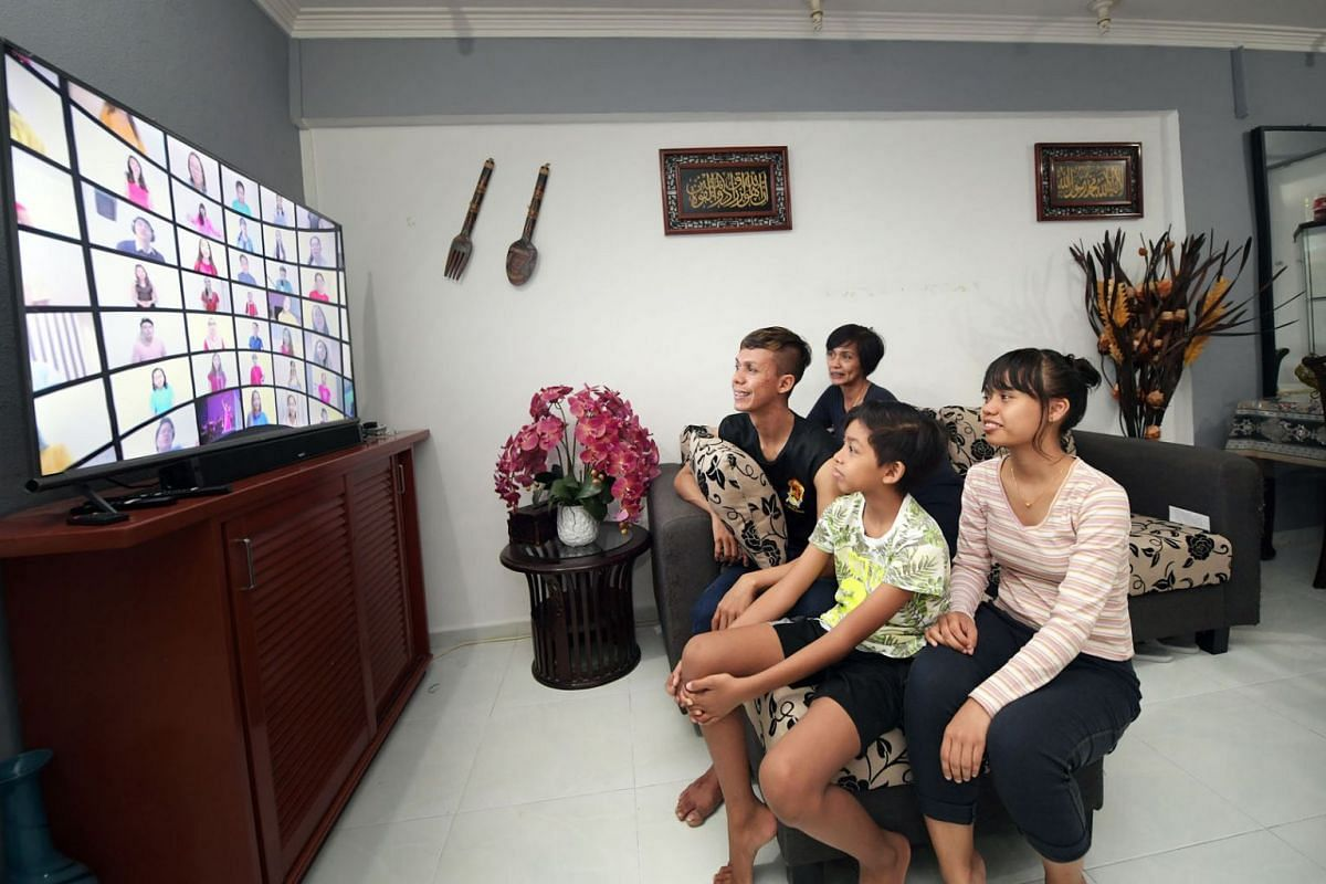 Miss Nur Quraisha Mohd Imran (far right), 18, a beneficiary of The Straits Times School Pocket Money Fund, watching ChildAid 2020 – Virtually Yours at home with her mother Ratenawati Omar, 52, and her brothers Muhammad Khairul Nizam, 29, and Muhamm