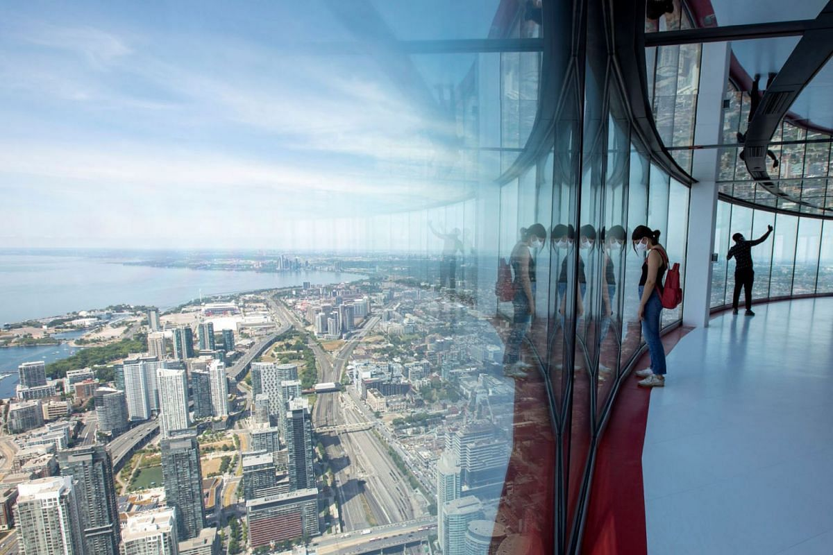 Visitors view panoramic city scenes from the 553 metres (1815 feet) high CN Tower, which reopened for the first time since the coronavirus disease restrictions were imposed in Toronto, Ontario, Canada, on July 15, 2020. PHOTO: REUTERS