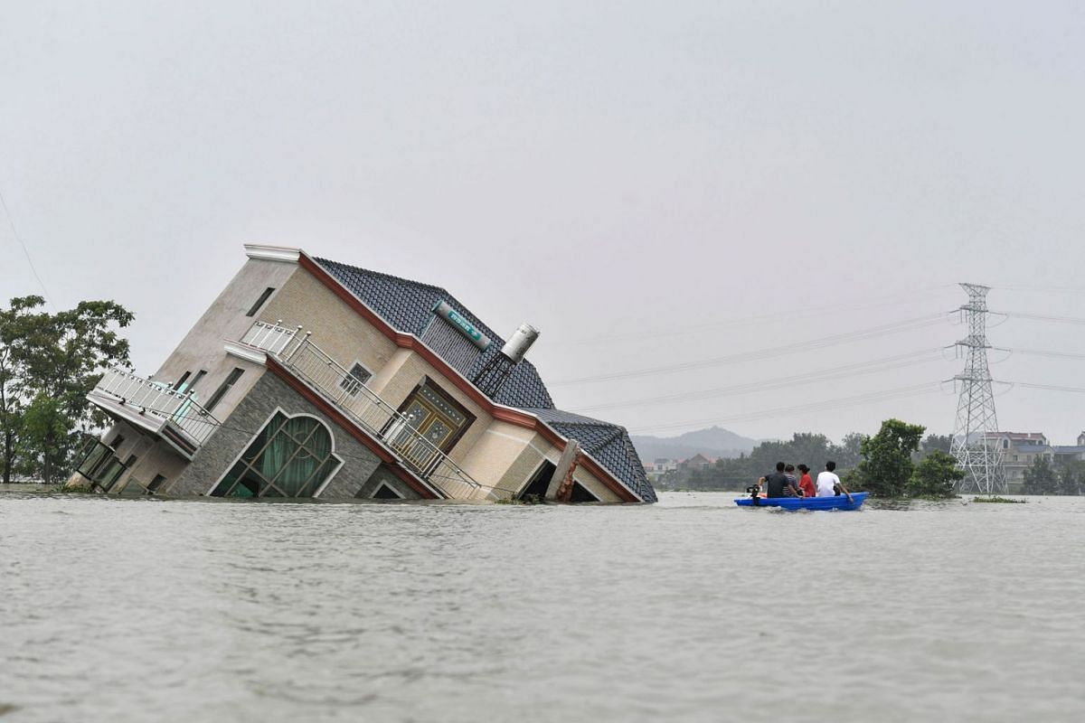 This photo taken on July 15, 2020 shows residents riding a boat past a damaged and flood-affected house near the Poyang Lake due to torrential rains in Poyang county, Shangrao city in China's central Jiangxi province. PHOTO: AFP