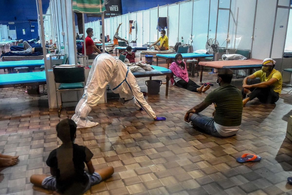 A doctor wearing a Personal Protective Equipment (PPE) suit (2L) instructs patients as they perform yoga inside a ward at the Commonwealth Games (CWG) Village sports complex, temporarily converted into a  coronavirus care centre, in New Delhi on July
