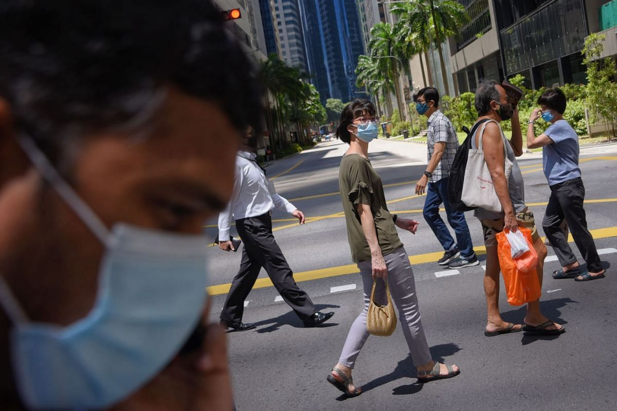 People wearing masks as a precaution against the coronavirus disease cross the road in Singapore's Central Business District (CBD) during lunch hours  on 16 July, 2020. PHOTO: THE STRAITS TIMES/MARK CHEONG