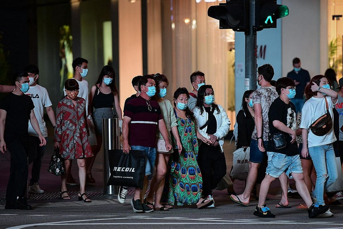Pedestrians outside The Heeren shopping centre in Orchard Road on Tuesday. Retailers are hoping online vouchers and flash deals will not only boost sales, but also help drive shoppers back to their physical stores.