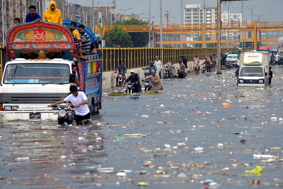 People wade through a flooded street after heavy monsoon rains in Karachi, Pakistan, on July 26, 2020.  PHOTO: AFP