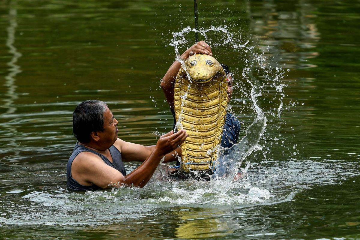 Hindu devotees pay respect by pouring water over a statue of the Hindu snake god known as 'Nag' during Naga Panchami, the traditional worship of snakes at Nagpokhari in Bhaktapur on the outskirts of Kathmandu on July 25, 2020. PHOTO: AFP