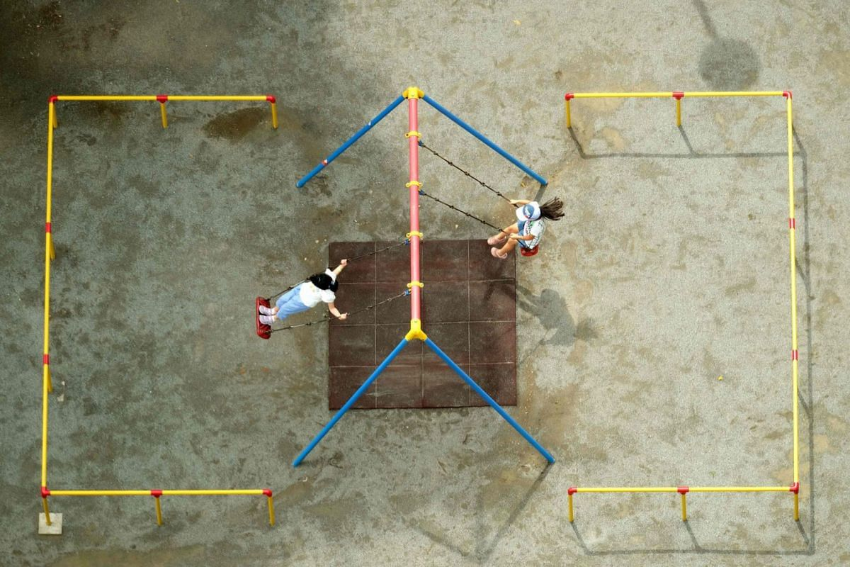 This overhead image shows children playing on swings at a park in Tokyo on July 26, 2020. PHOTO: AFP