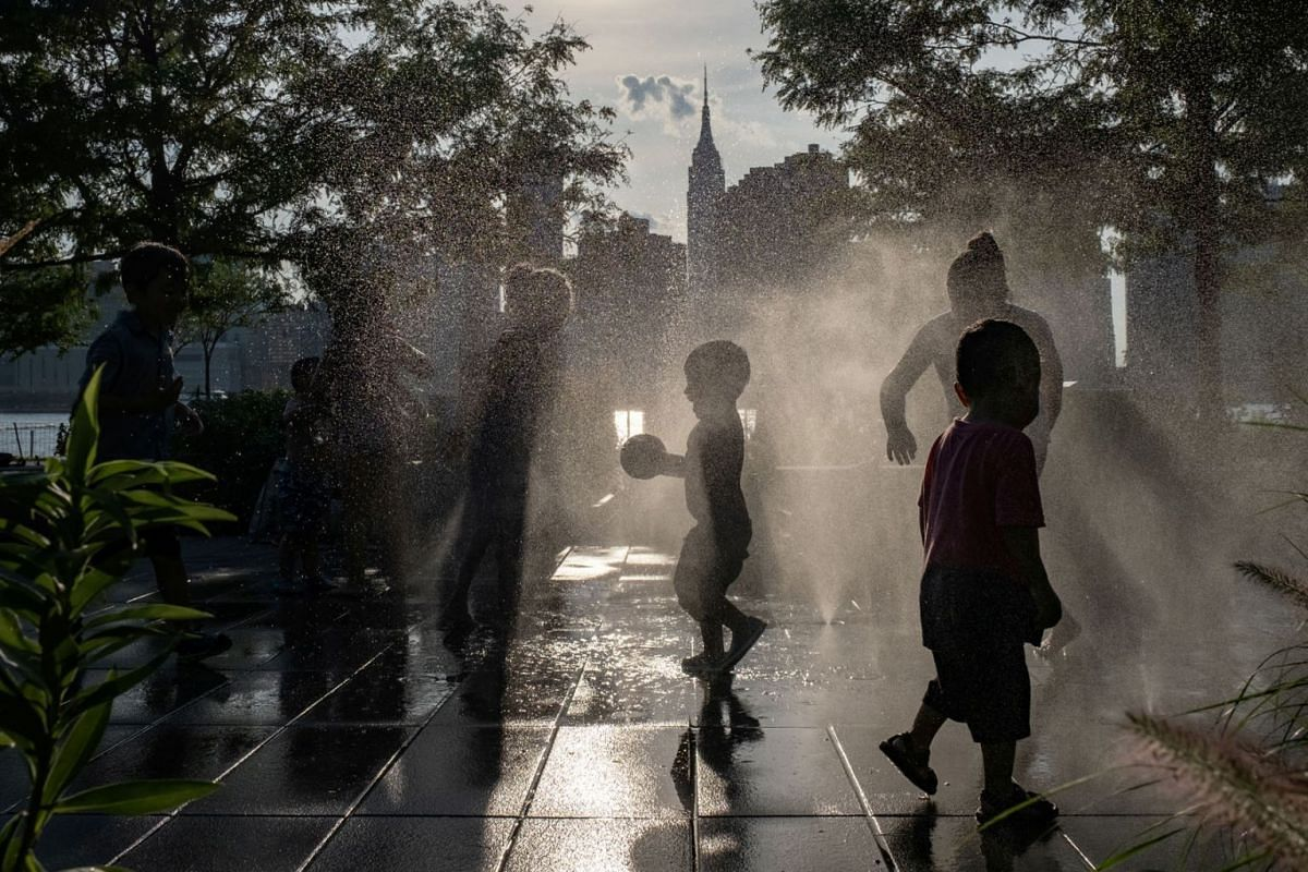 Children cool off in a fountain while enjoying a warm and humid day at Gantry Plaza State Park following the outbreak of the coronavirus disease, in Long Island City, New York, U.S., July 25, 2020. PHOTO: REUTERS