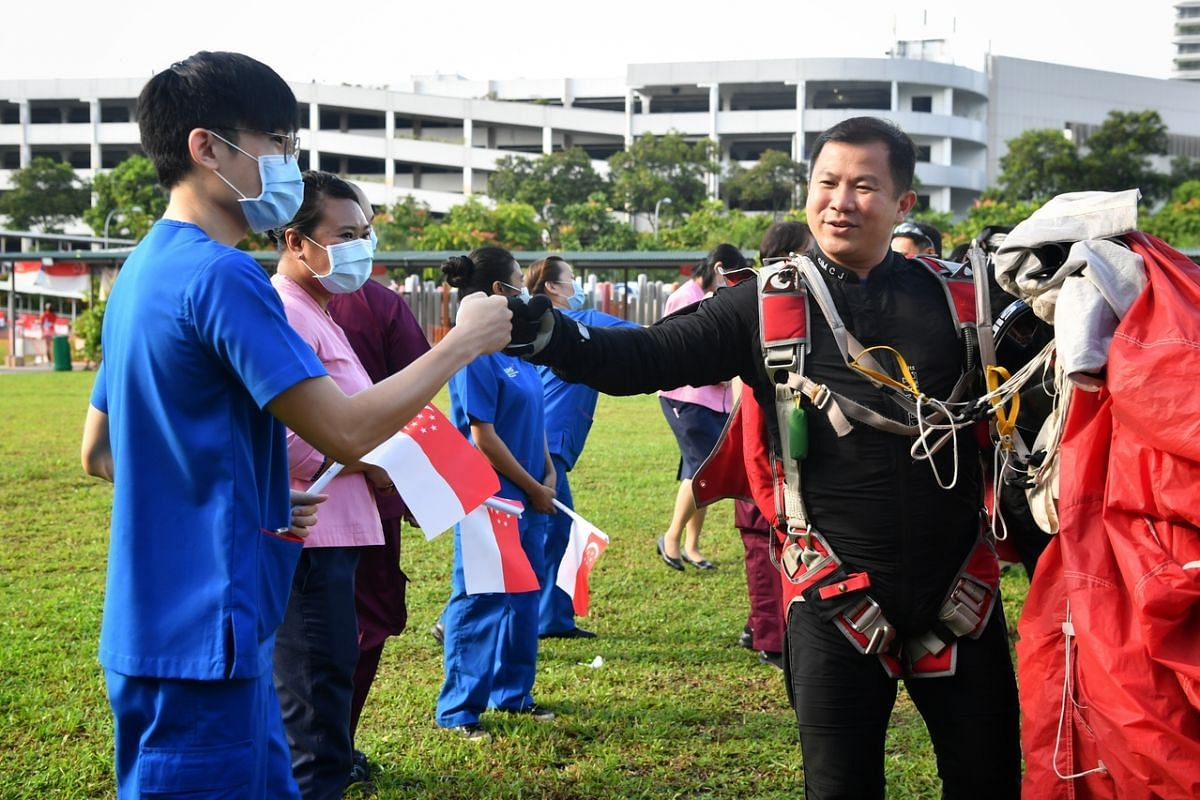 Red Lions exchange fist bumps with healthcare workers after landing at the grass patch near Block 285C Toh Guan Road during the NDP rehearsal on July 26, 2020.