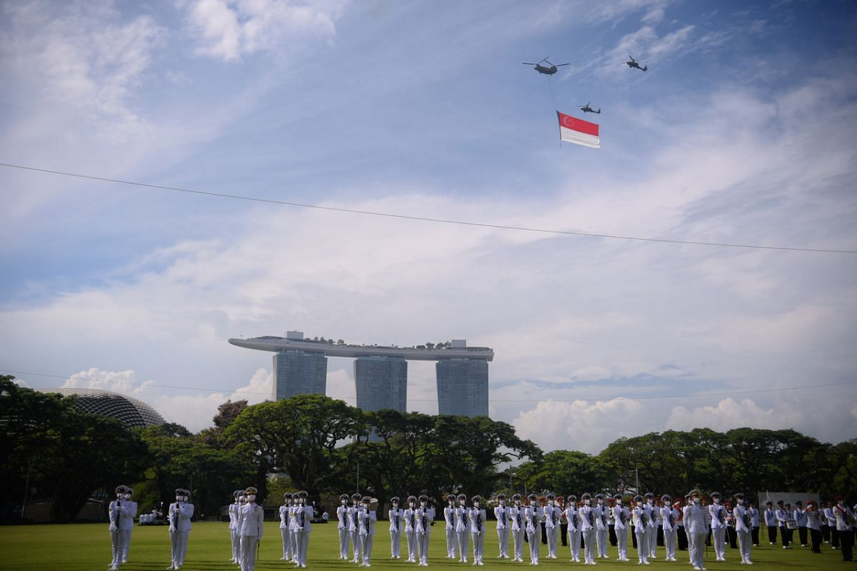 The state flag flypast is seen in the background of the marching contingents during the NDP rehearsal at the Padang on July 26, 2020.