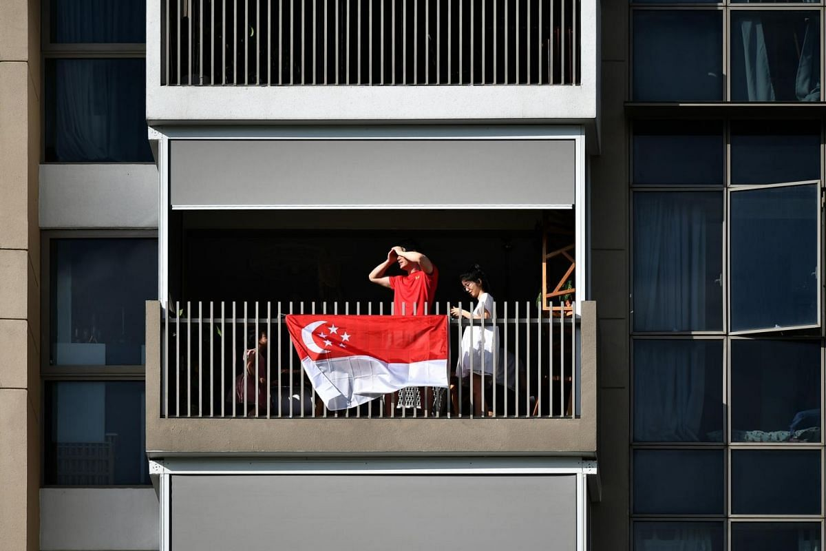 Residents of executive condominium The Vales looking out for the arrival of the Red Lions landing at an open field near Sengkang General Hospital during the NDP rehearsal on July 26, 2020.