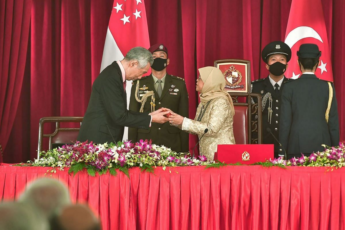 Prime Minister Lee Hsien Loong receiving the instrument of appointment from President Halimah Yacob at the Istana on July 27, 2020, during the swearing-in ceremony for the Prime Minister and other Cabinet ministers. PHOTO: THE STRAITS TIMES/DESMOND W