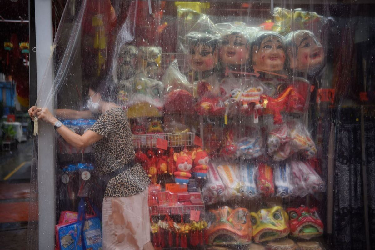 A shopkeeper covering her wares with a plastic sheet at a shop in Chinatown, just before a heavy downpour at around 1pm on July 27, 2020. PHOTO: THE STRAITS TIMES/MARK CHEONG