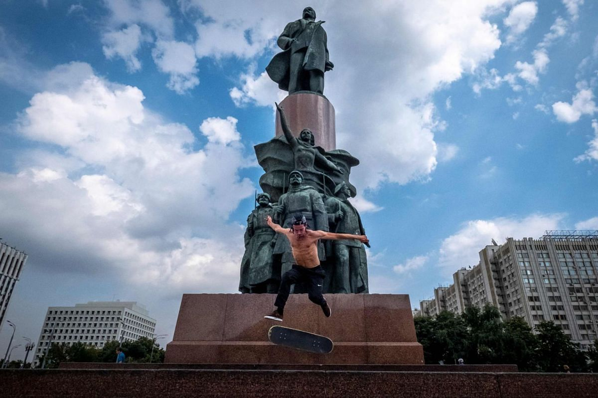 A skateboarder performs a trick in front of a monument to the Soviet Union founder Vladimir Lenin in Moscow on July 27, 2020. PHOTO: AFP