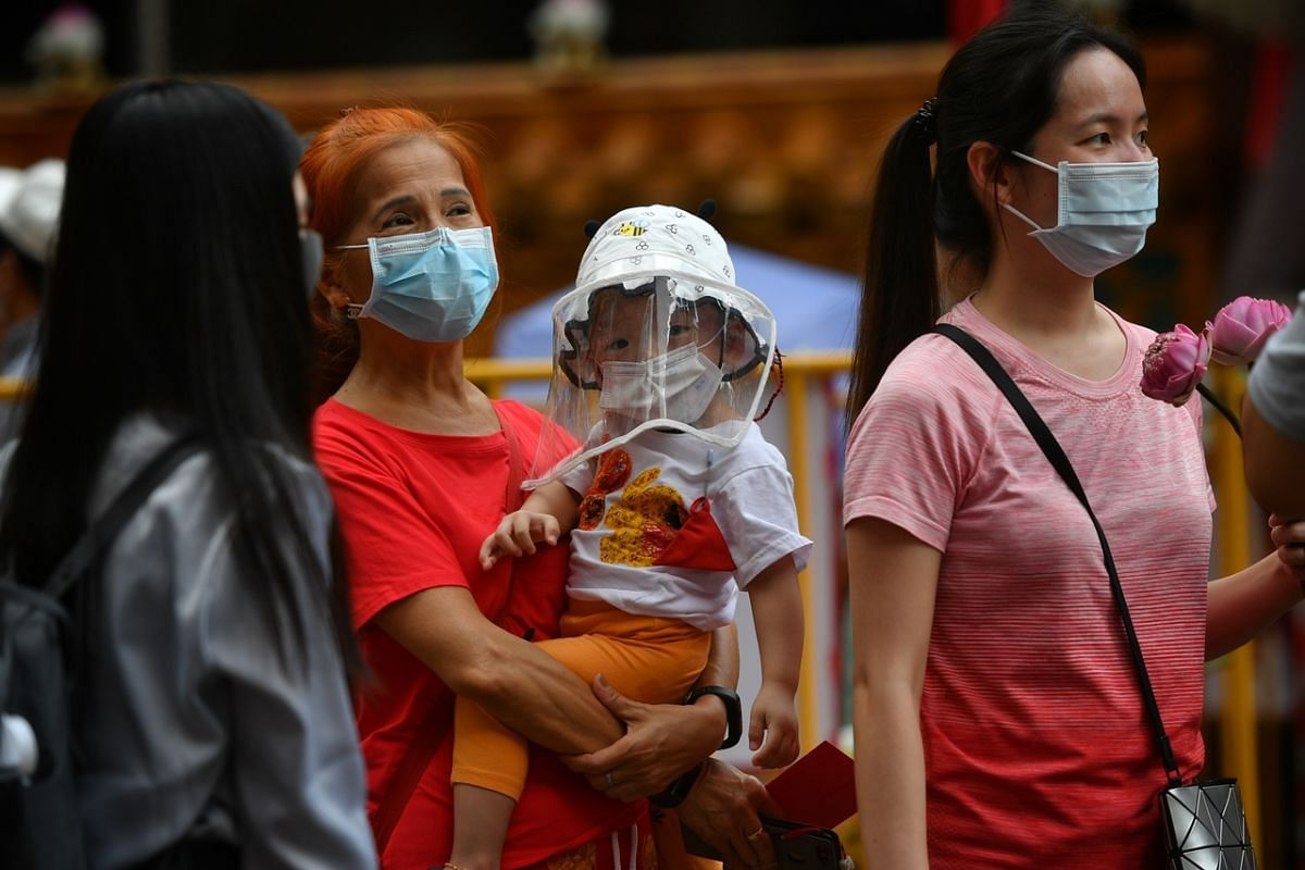 A young worshipper and relatives leaving the Kwan Im Thong Hood Cho Temple in Waterloo Street on July 27, 2020.