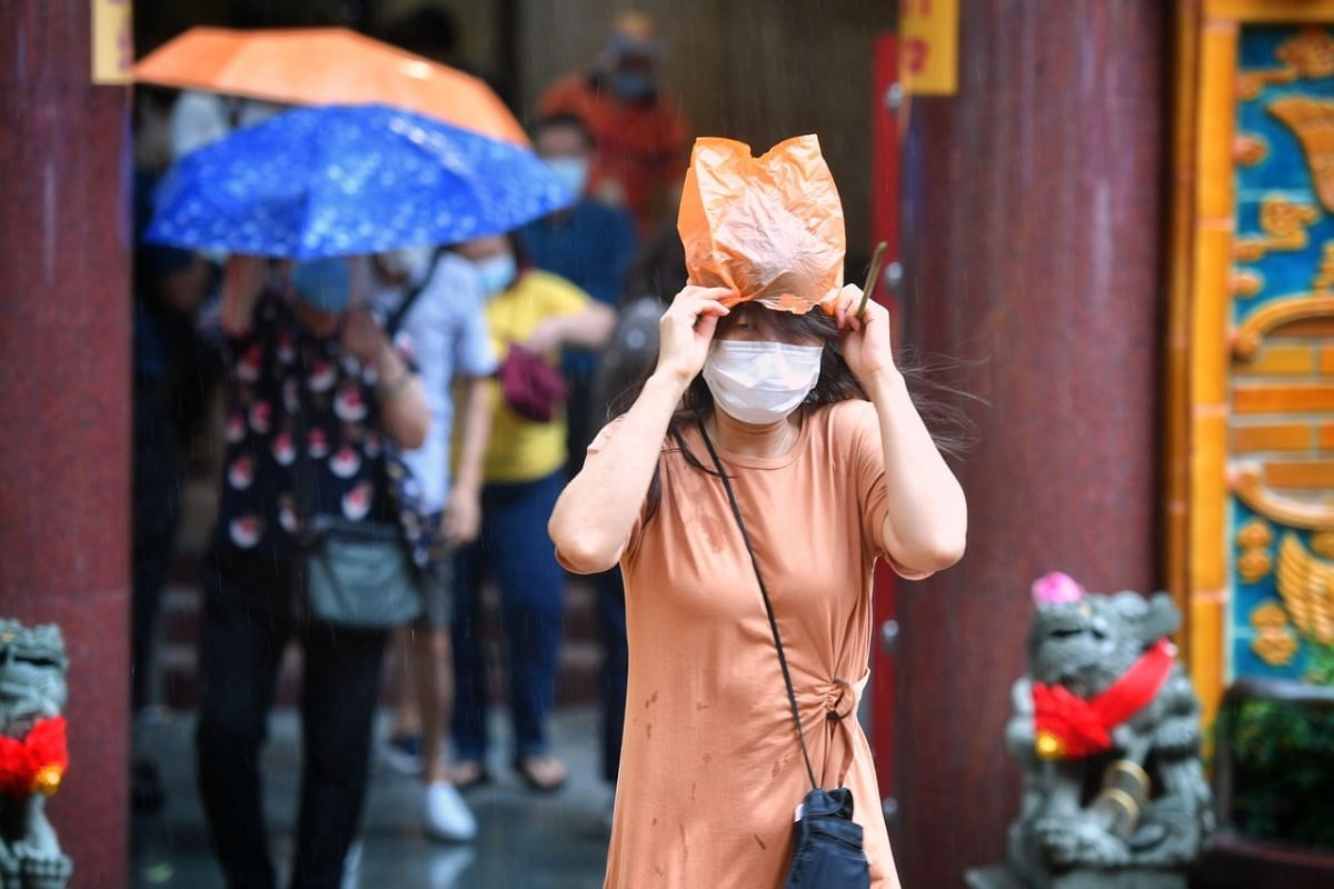 Sudden rain catching worshippers off guard at the Kwan Im Thong Hood Cho Temple in Waterloo Street on July 27, 2020.