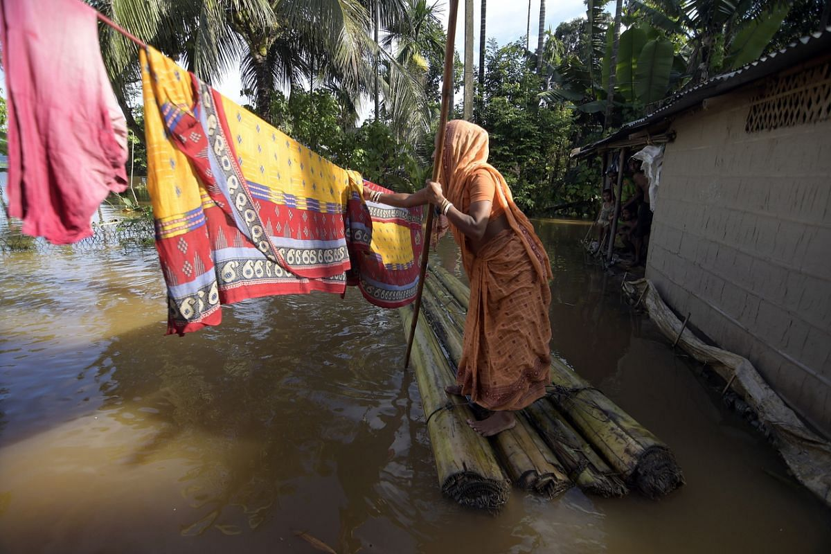 A woman hanging her clothes to dry outside her submerged house after a flood in India's Assam state on July 23, 2020.