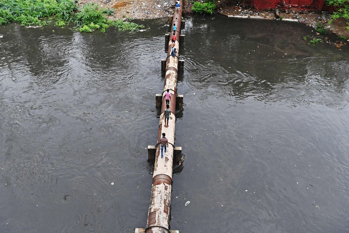 People walking across an elevated water pipeline over a flooded sewage canal after a monsoon rain in New Delhi on July 22, 2020.