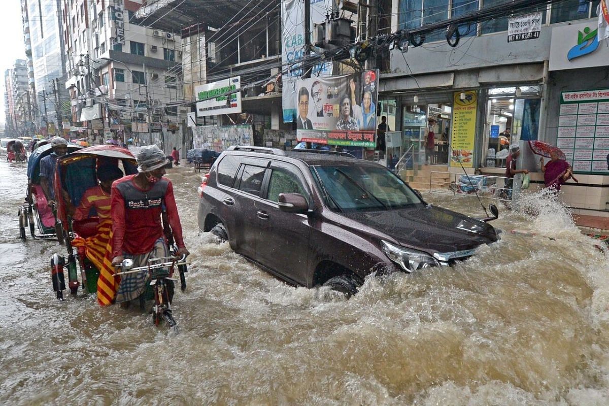 Commuters making their way through a water-logged street after a heavy downpour in Dhaka, Bangladesh, on July 21, 2020.