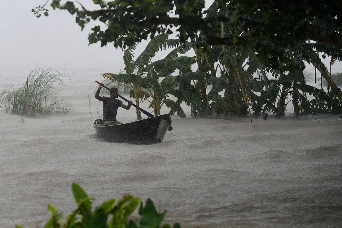 A man rows a boat in flood waters in Dohar, Bangladesh, on July 20, 2020.