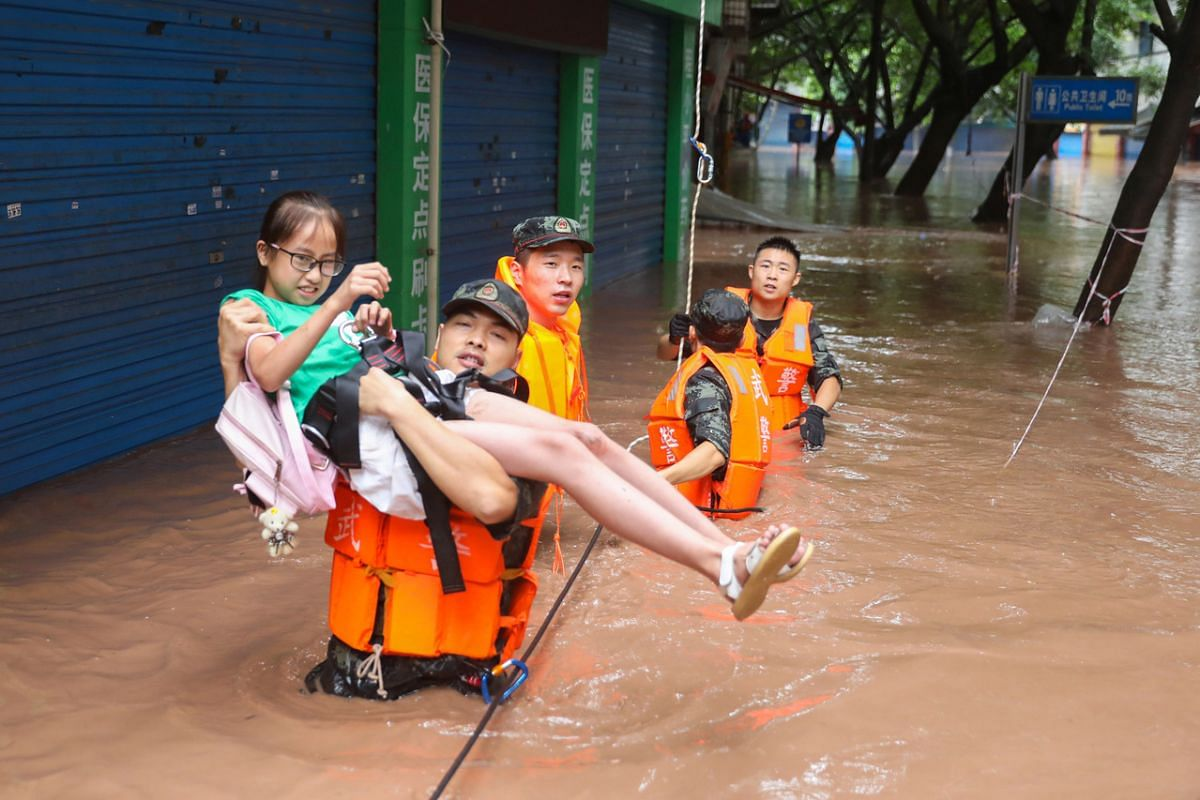 A paramilitary police officer evacuating a resident following heavy rainfall in Wanzhou, China, on July 16, 2020.