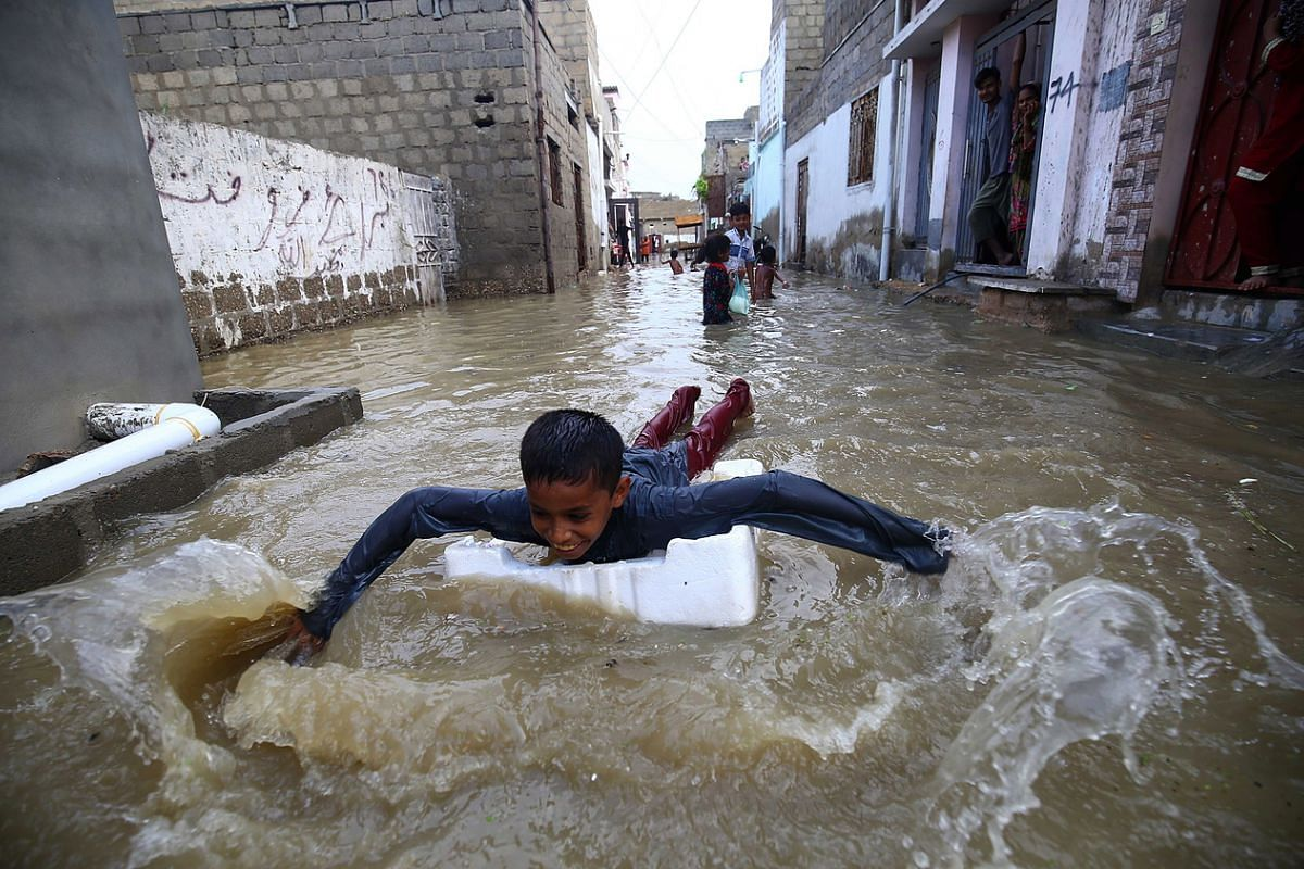 Children playing in a flooded street after heavy rain in Karachi, Pakistan, on July 26, 2020.