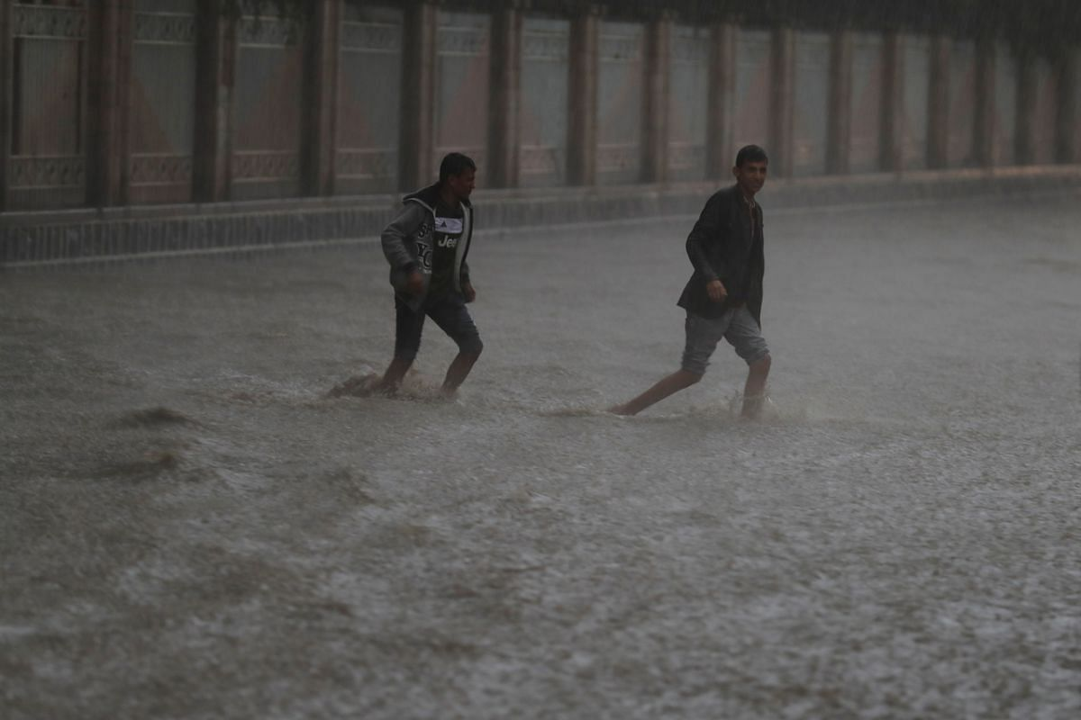 Yemenis attempting to cross a flooded street during heavy rainfall in Sana'a, Yemen, on July 28, 2020. Heavy rain and associated floods have hit the country in the last few days, killing at least 14 people and destroying dozens of houses and roads.