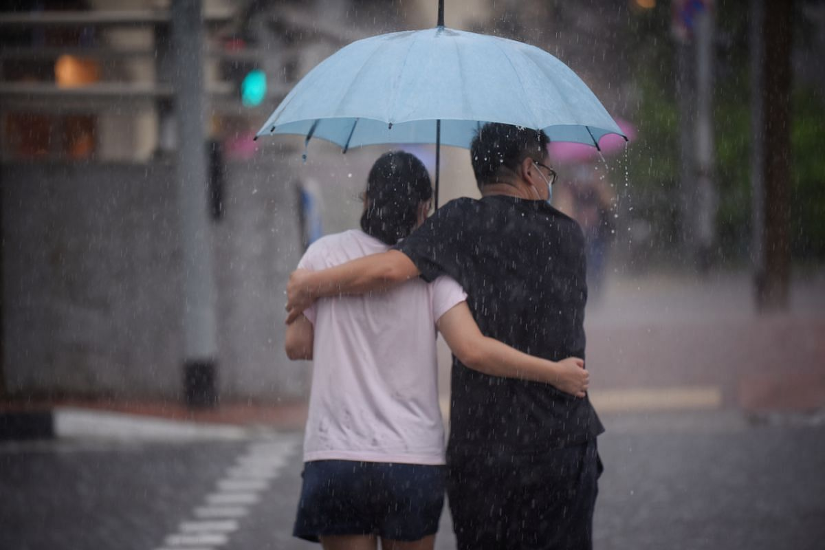 Pedestrians crossing the road in Singapore's Chinatown during a downpour on July 27, 2020.
