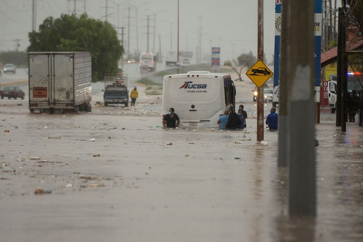People wading through floodwater caused by heavy rain in the Mexcian city of Saltillo on July 26, 2020. The tropical storm Hanna flooded several cities in north-eastern Mexico.