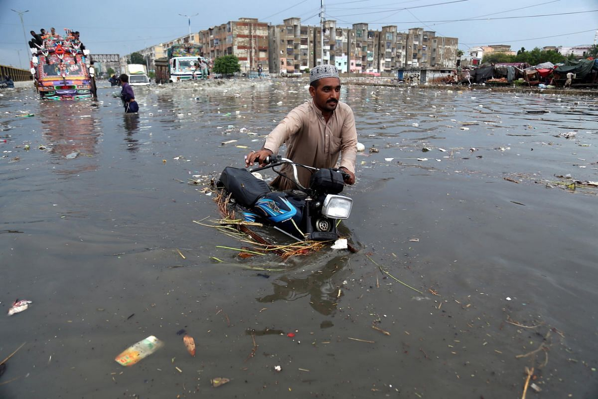 Motorcyclists making their way through a flooded road after heavy rain in Karachi, Pakistan, on July 26, 2020.